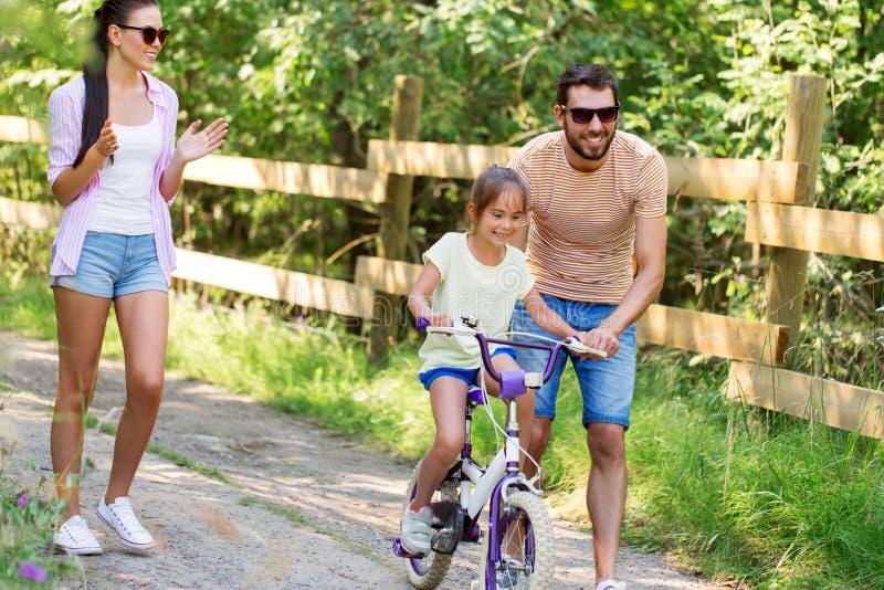 Ungen med patent som lär att rida cykeln parkerar in arkivfoto