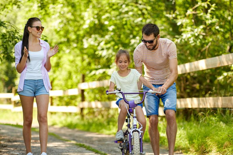 Ungen med patent som lär att rida cykeln parkerar in royaltyfria foton