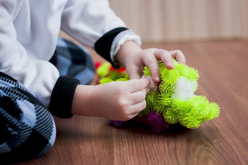 Ungen modellerar en grön lastbilmaskin från kulöra klistermärkebollar royaltyfria bilder