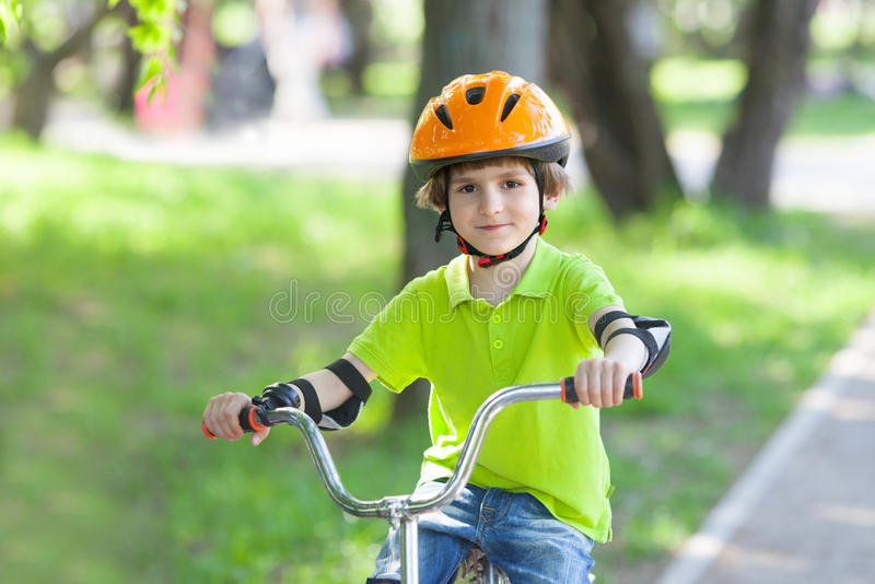 Ungen rider en cykel royaltyfria bilder