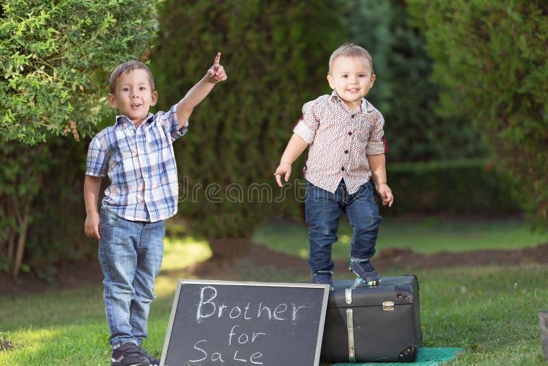 Ungen säljer din broder i parkera arkivbilder