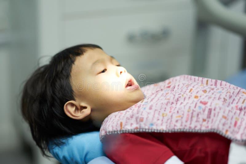 Ungen väntar på undersökande tandbehandling av tandläkaren och assistenten royaltyfri foto