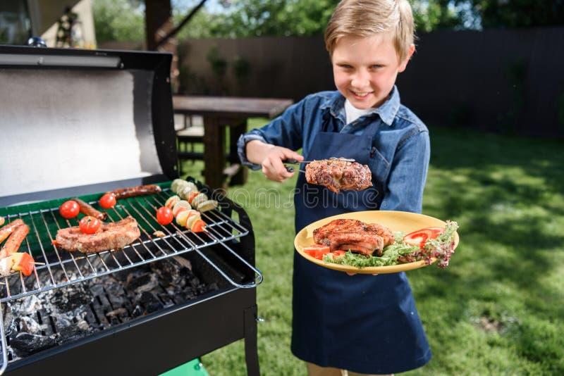 Ungepojke i förklädet som utomhus förbereder smakliga insatser på grillfestgaller arkivbild