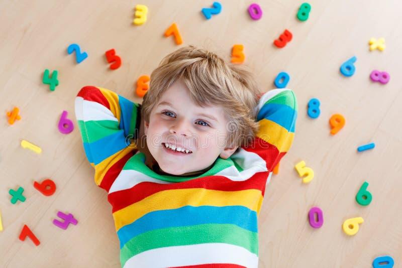 Ungepojke med färgrika nummer, inomhus arkivbild