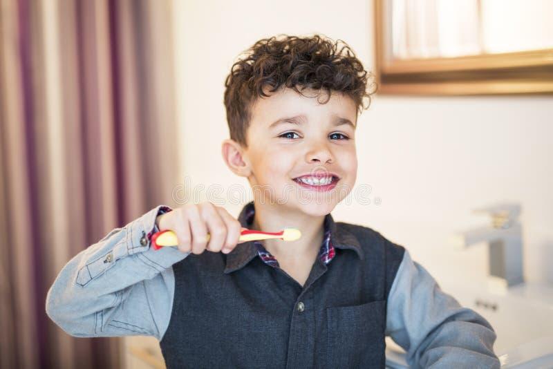 Ungepojke som borstar tänder royaltyfri foto