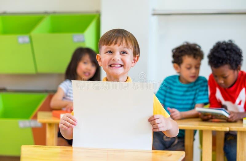 Ungepojke som rymmer tomt papper med baksida till skolaordet med den mångfaldvänner och läraren på bakgrund, dagisskola som är fa royaltyfri foto