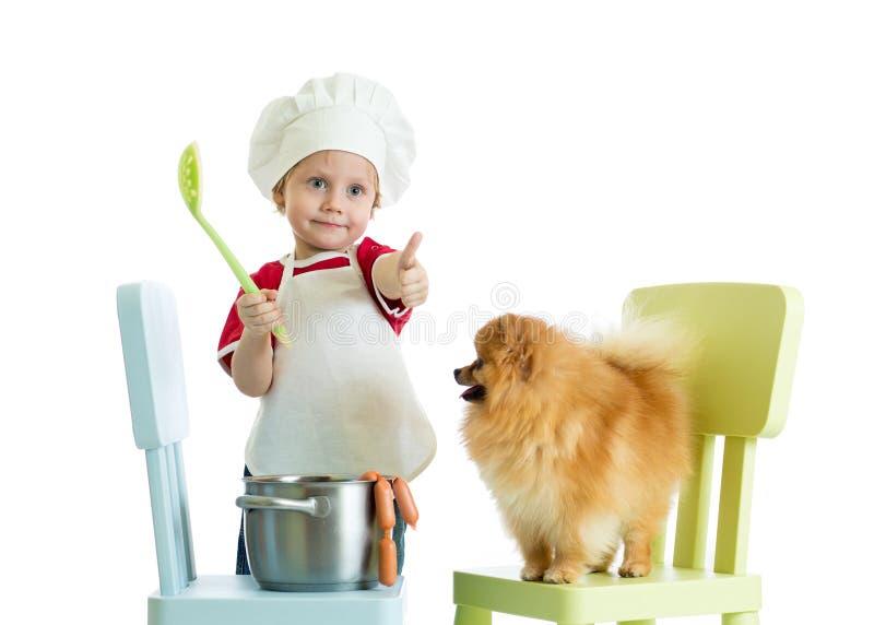 Ungepojke som spelar kocken med hunden Barnet weared kocken matar Spitzvalpen arkivfoton