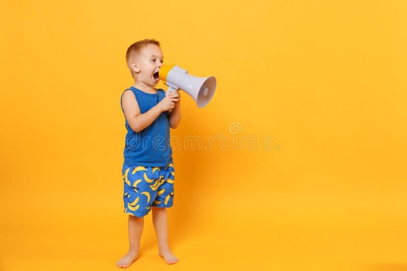 Ungepojken 3-4 gamla år i blå håll för strandsommarkläder talar i megafonen som isoleras på ljus gul orange bakgrund royaltyfri fotografi