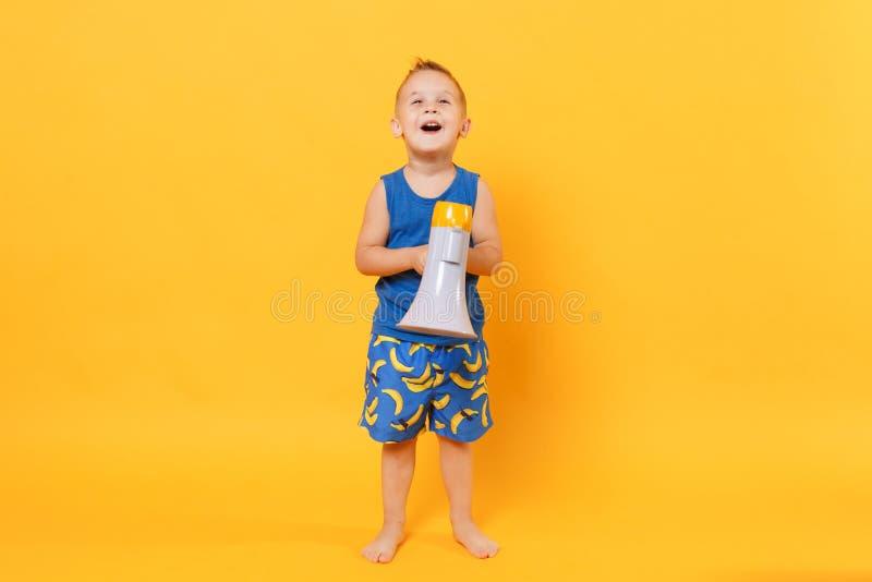 Ungepojken 3-4 gamla år i blå håll för strandsommarkläder talar i megafonen som isoleras på ljus gul orange bakgrund royaltyfria foton