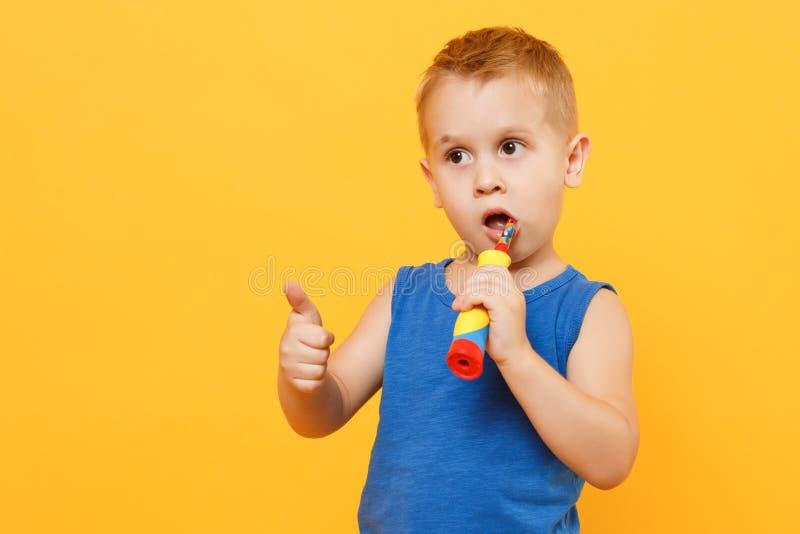 Ungepojken 3-4 gamla år i blå skjorta borstar hans tänder med tandborsten som isoleras på ljus gul orange väggbakgrund royaltyfri foto