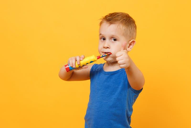 Ungepojken 3-4 gamla år i blå skjorta borstar hans tänder med tandborsten som isoleras på ljus gul orange väggbakgrund arkivbilder