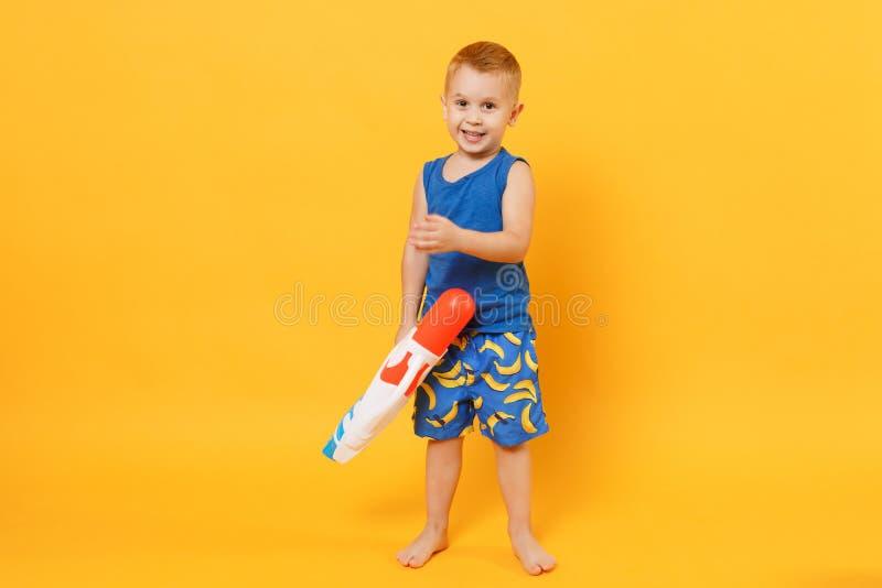 Ungepojken 3-4 gamla år i blå strandsommarkläder rymmer leksakvattenvapnet isolerat på ljus gul orange väggbakgrund fotografering för bildbyråer
