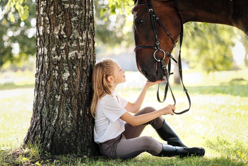 Ungerska jockey sitter i en grön rensning under ett träd Matar en häst och ett äpple och slår det royaltyfri foto