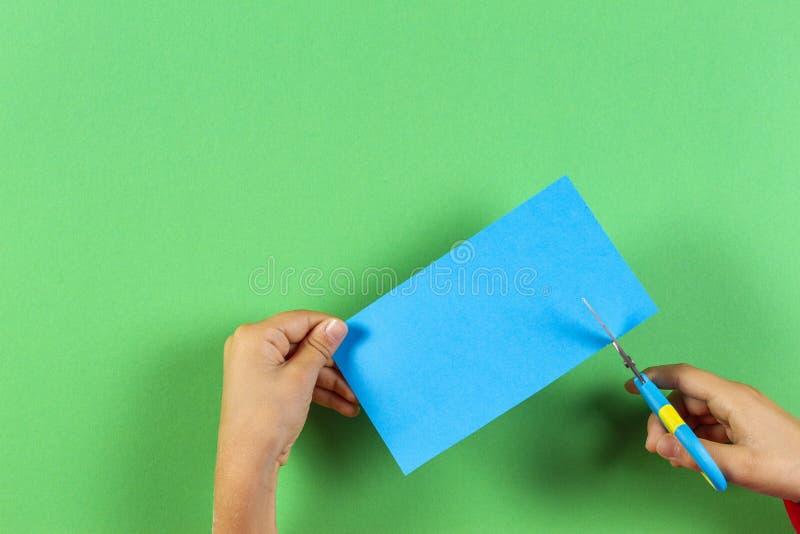 Unges händer som klipper ett ark av blått papper genom att använda sax över grön bakgrund arkivfoton