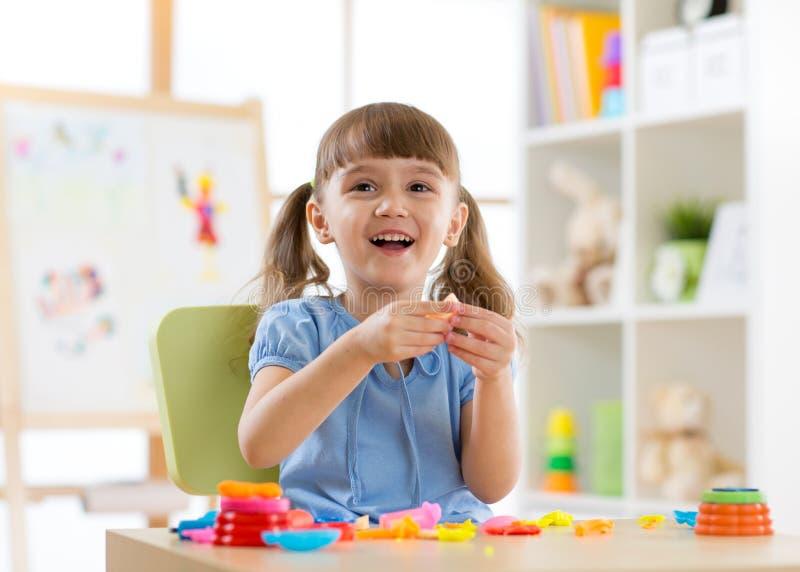 Unges kreativitet barnlera sculpts Den lyckliga lilla flickan gjuter från plasticine på tabellen royaltyfri foto