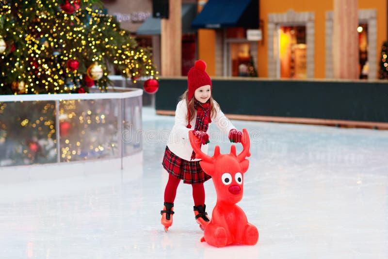 Ungeskridskoåkningen i vinter parkerar isbanan Barnisskridsko på ganska jul Liten flicka med skridskor på kall dag Utomhus- gycke royaltyfri fotografi