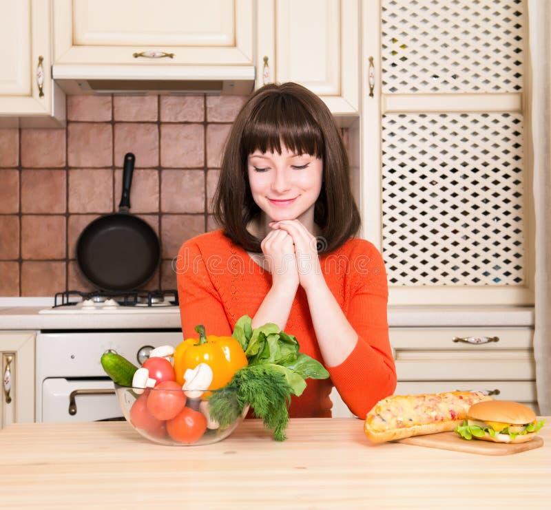 Ungesund gegen gesunde Lebensmittelkonzeptfrau mit Gemüseausschuß stockfotos