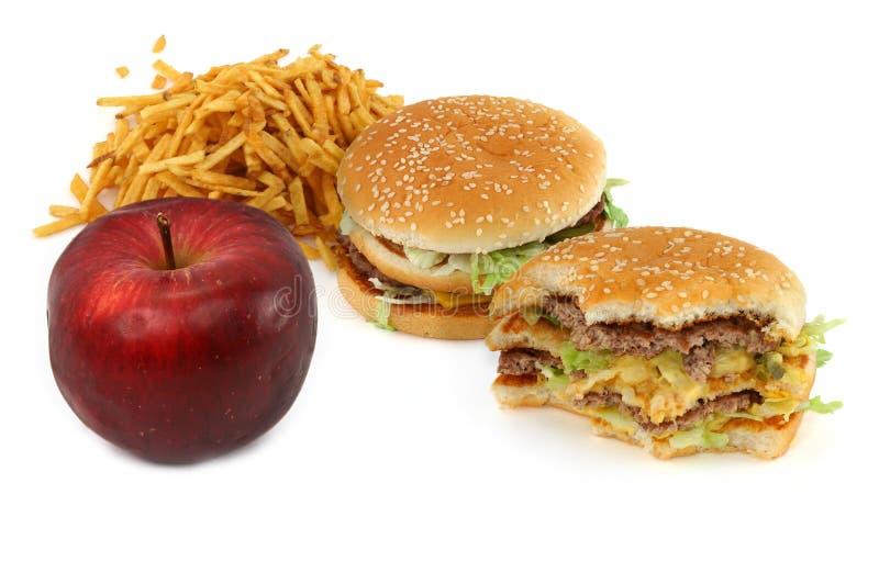 Ungesunde Fertigkost und Apfel lizenzfreie stockfotos
