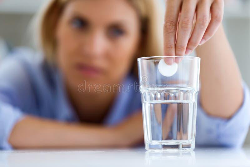 Ungesunde junge Frau, die zu Hause ein Glas mit einer schäumenden Pille betrachtet lizenzfreies stockfoto
