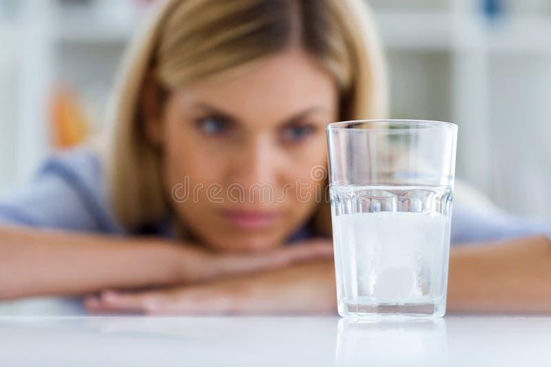 Ungesunde junge Frau, die zu Hause ein Glas mit einer schäumenden Pille betrachtet stockfotografie