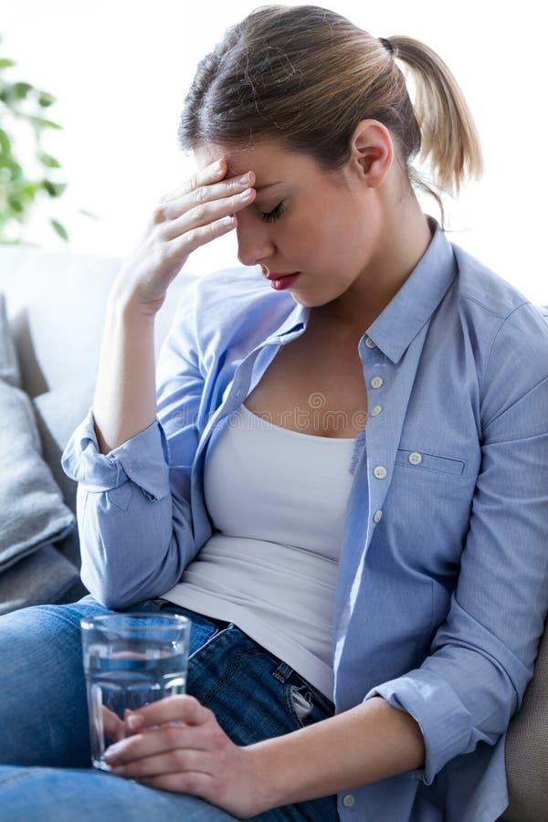 Ungesunde junge Frau mit den Kopfschmerzen, die Glas Wasser beim auf Sofa zu Hause sitzen halten stockbilder
