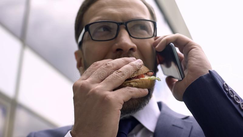 Ungesunde Nahrung, beschäftigter Geschäftsmann, der am Telefon spricht und das Burgermittagessen isst lizenzfreies stockbild