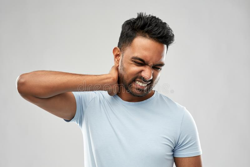 Ungesunder indischer Mann, der unter Nackenschmerzen leidet lizenzfreie stockbilder