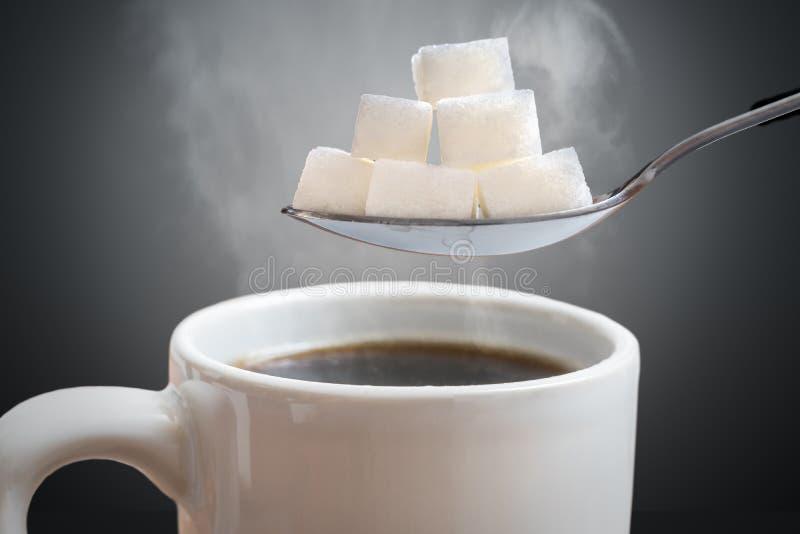 Ungesundes Essenkonzept Viele zuckern Würfel über heißer Tasse Tee oder Kaffee lizenzfreies stockfoto