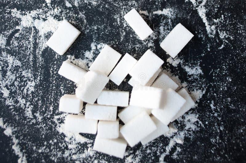 Ungesundes Lebensmittelkonzept - Zucker und Mehl auf einem schwarzen Hintergrund lizenzfreies stockbild