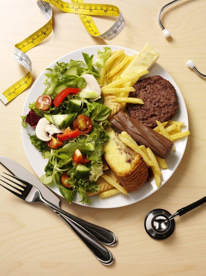 Ungesundes und gesundes Lebensmittel auf einer Platte stockbilder
