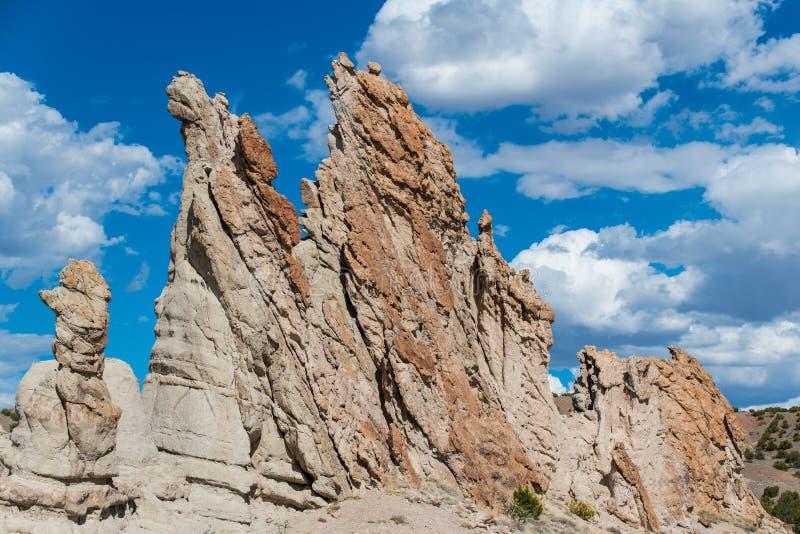 Ungewöhnliche, craggy Felsformationen und schroffe Berggipfel unter einem schönen blauen Himmel mit weißen geschwollenen Wolken lizenzfreie stockfotos