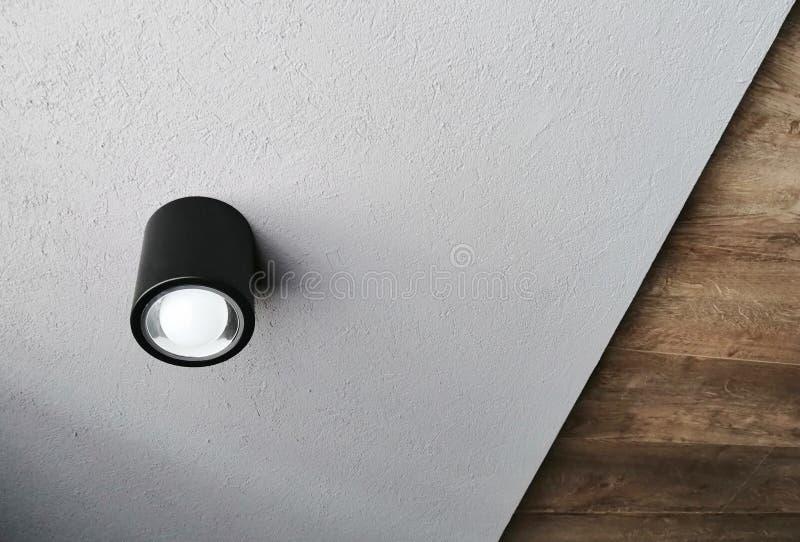 Ungewöhnliche Decke mit einer modernen Lampe und verschiedenen Niveaus stockfoto