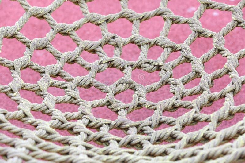 Ungewöhnliches gelbes Seil geknotet im Park und im Schutznetz lizenzfreie stockfotografie