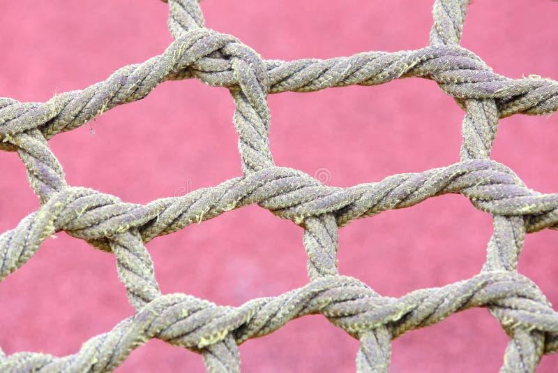Ungewöhnliches gelbes Seil geknotet im Park und im Schutznetz lizenzfreies stockbild