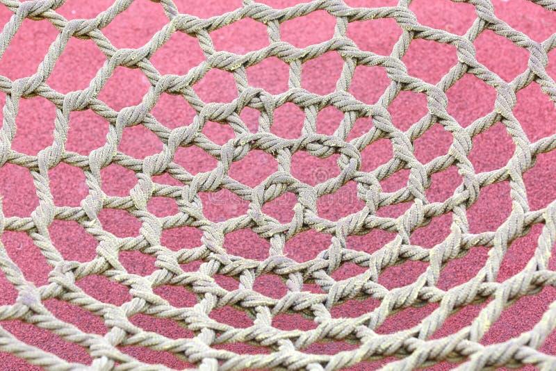 Ungewöhnliches gelbes Seil geknotet im Park und im Schutznetz lizenzfreie stockfotos