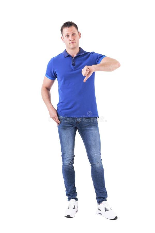 Ungewisser verwirrter erwachsener Mann im blauen Polohemd, das unten Daumen zeigt und oben zweifelhaft schaut stockfotos