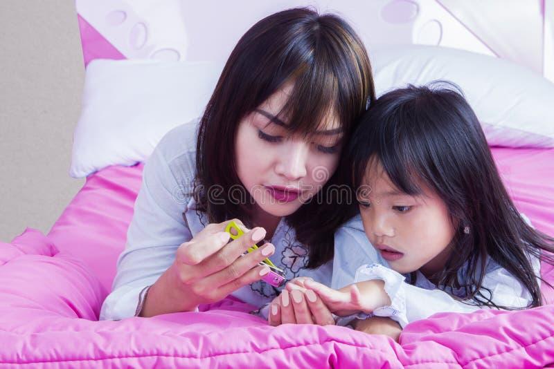 Unghia di taglio della madre sua figlia sul letto immagini stock