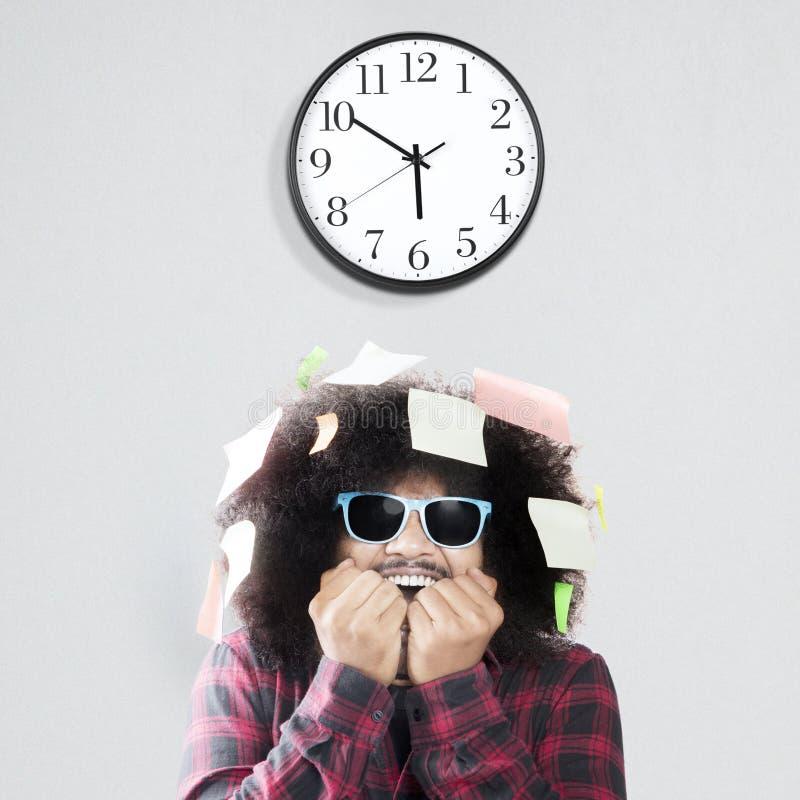 Unghia mordace dell'uomo impaurito con l'orologio di parete immagini stock