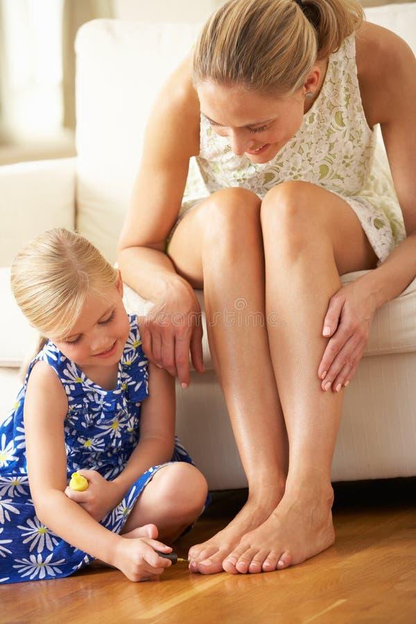 Unghie del piede della madre della pittura della figlia nel paese immagine stock