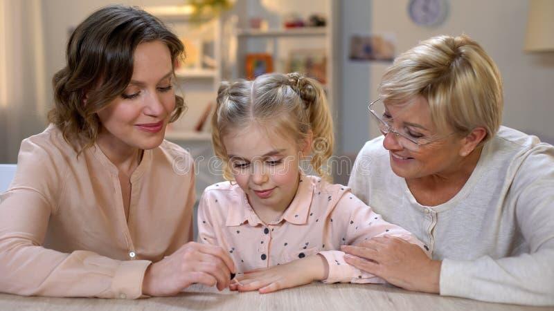 Unghie di amore della figlia della pittura della madre con lucidatura rosa, unità di tempo della famiglia immagini stock libere da diritti