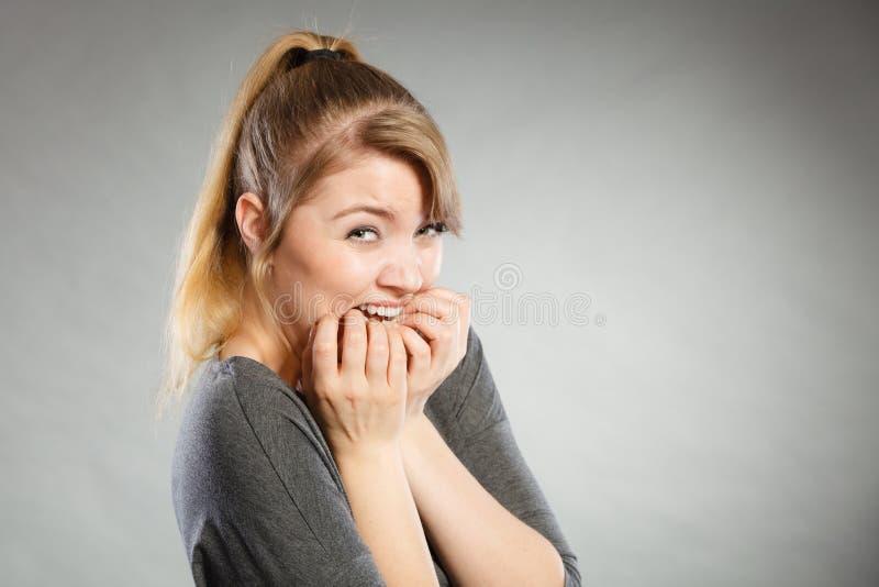 Unghie mordaci della ragazza nervosa fotografia stock
