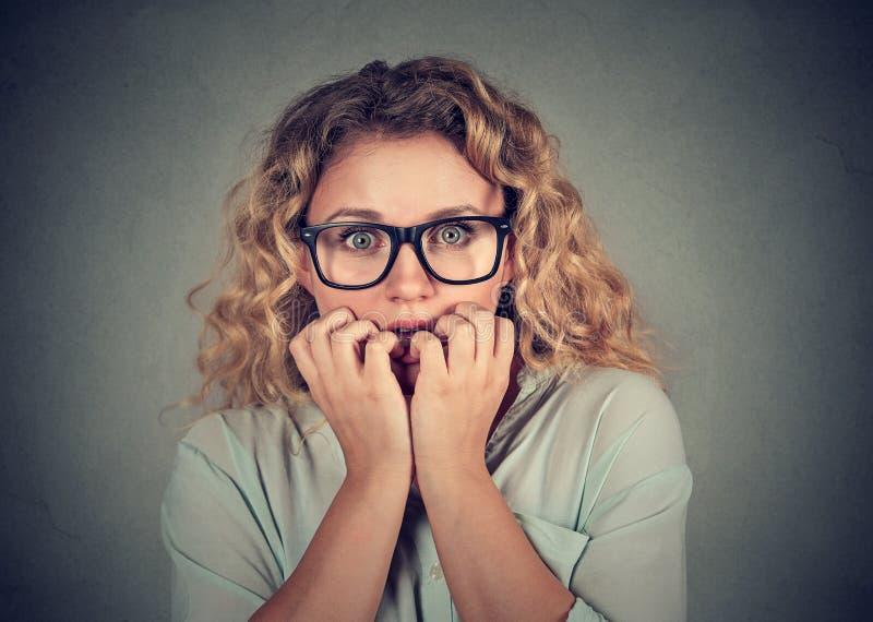 Unghie mordaci sollecitate nervose della giovane donna che guardano ansiosamente immagine stock libera da diritti