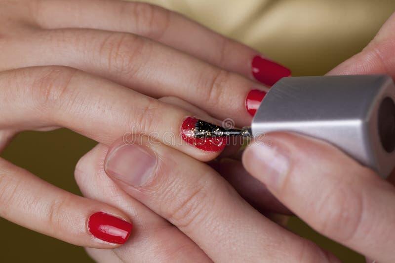 Unghie rosse del dito con scintille dorate fotografie stock libere da diritti