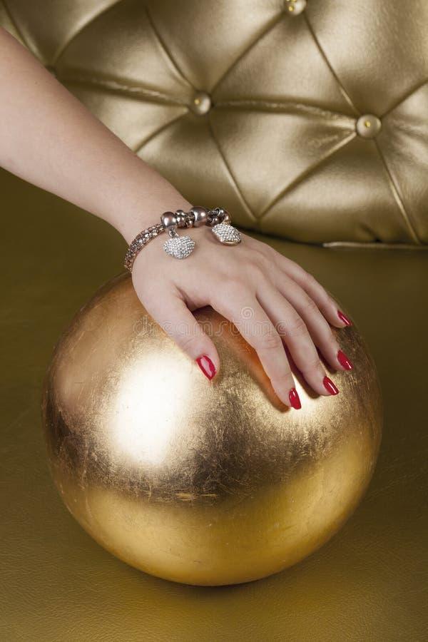 Unghie rosse del dito su una palla dorata fotografia stock