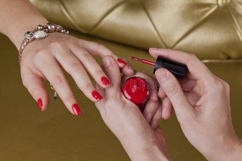 Unghie rosse del dito in un centro cosmetico fotografie stock libere da diritti