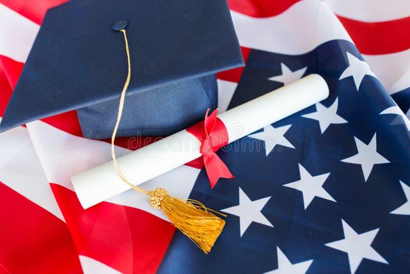 Ungkarlhatt och diplom på amerikanska flaggan royaltyfria foton
