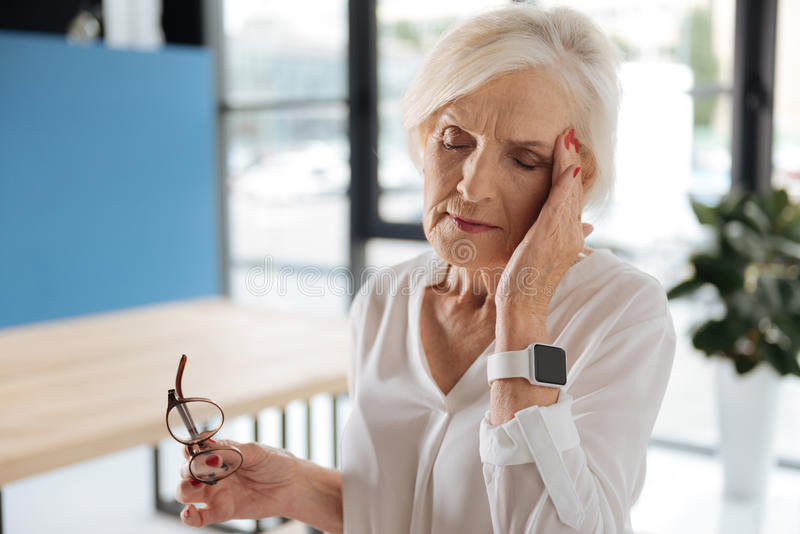 Unglückliche ältere Frau, die ihren Tempel hält stockfotografie