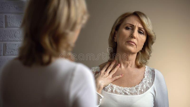 Unglückliche ältere Frau, die im Spiegel schaut und decollete Zone, Falten berührt stockbild