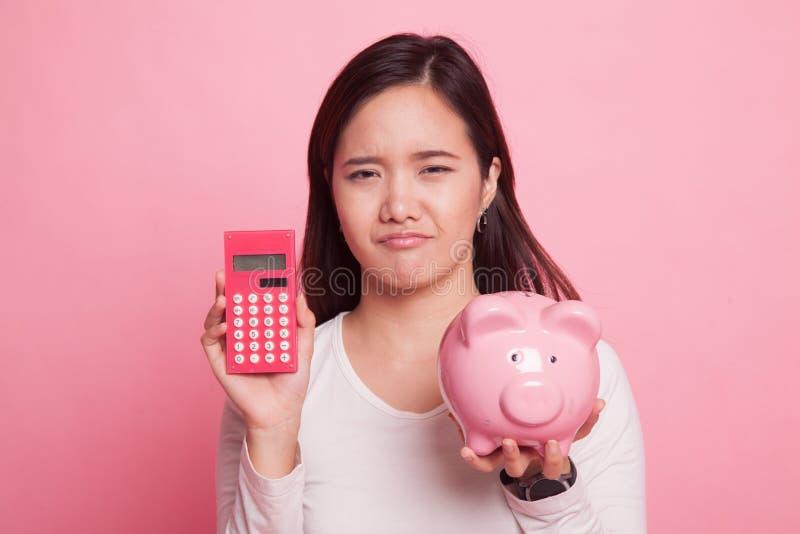Unglückliche Asiatin mit Taschenrechner und Sparschwein lizenzfreie stockfotos