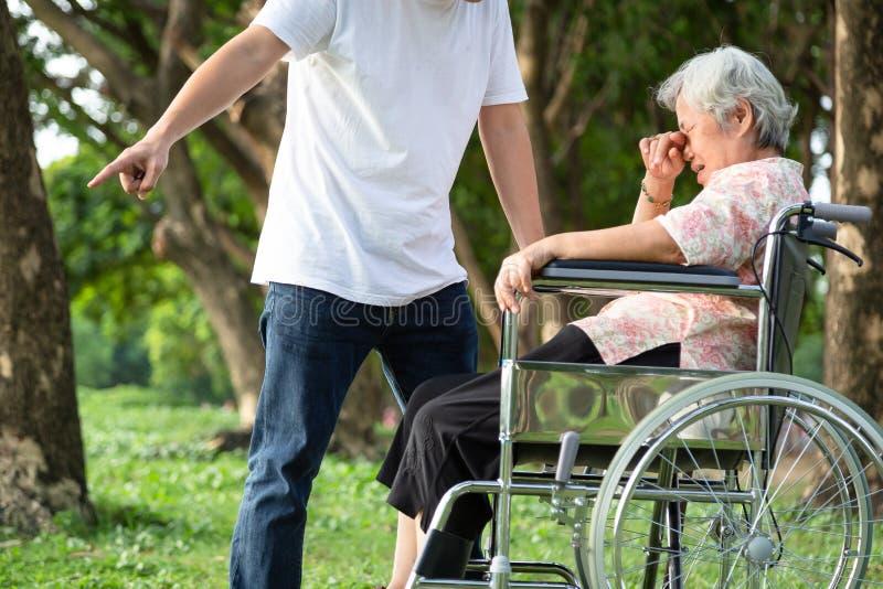 Unglückliche, der Probleme asiatische Familie, verärgerter Mann oder männliche Pflegekraft trieben seine ältere Frau im Rollstuhl stockfoto